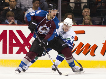 VANCOUVER, CANADA - OCTOBER 26: Christian Ehrhoff #5 of the Vancouver Canucks tries to poke the puck away from TJ Galiardi #39 of the Colorado Avalanche during the third period in NHL action on October 26, 2010 at Rogers Arena in Vancouver, British Columb
