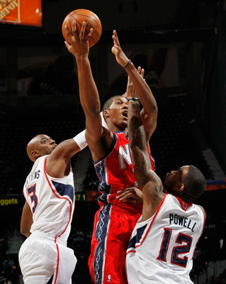 ATLANTA, GA - DECEMBER 07:  Damien Wilkins #3 and Josh Powell #12 of the Atlanta Hawks defend the basket against Derrick Favors #14 of the New Jersey Nets at Philips Arena on December 7, 2010 in Atlanta, Georgia.  NOTE TO USER: User expressly acknowledges
