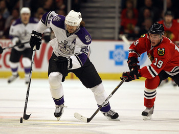 CHICAGO, IL - DECEMBER 19: Michal Handzus #26 of the Los Angeles Kings skates up the ice under pressure from Jonathan Toews #19 of the Chicago Blackhawks at the United Center on December 19, 2010 in Chicago, Illinois. The Blackhawks defeated the Kings 3-2
