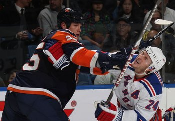 UNIONDALE, NY - DECEMBER 17: Brandon Dubinsky #24 of the New York Rangers is hit by Andy Sutton #25 of the New York Islanders at the Nassau Coliseum on December 17, 2009 in Uniondale, New York. The Rangers defeated the Islanders 5-2. (Photo by Bruce Benne