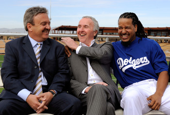 GLENDALE, AZ - MARCH 05:  Manny Ramirez#99 (R) hugs owner Frank McCourt as general manager Ned Colletti looks on during a news conference on March 5, 2009, at Camelback Ranch in Glendale, Arizona. Ramirez signed a $45 million two-year contract on Wednesda