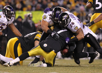 PITTSBURGH, PA - JANUARY 15:  Quarterback Ben Roethlisberger #7 of the Pittsburgh Steelers is sacked by safety Dawan Landry #26 and defensive tackle Haloti Ngata #92 of the Baltimore Ravens during the AFC Divisional Playoff Game at Heinz Field on January