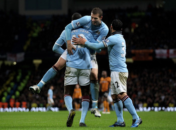 MANCHESTER, ENGLAND - JANUARY 15:  Yaya Toure of Manchester City celebrates scoring his team's third goal with team mates Edin Dzeko and Carlos Tevez (R) during the Barclays Premier League match between Manchester City and Wolverhampton Wanderers at the C