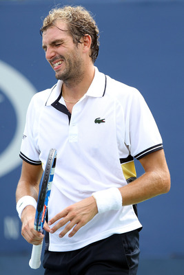 NEW YORK - SEPTEMBER 03:  Julien Benneteau of France grimaces after injuring his wrist while playing against Tommy Robredo of Spain during his men's singles match on day five of the 2010 U.S. Open at the USTA Billie Jean King National Tennis Center on Sep