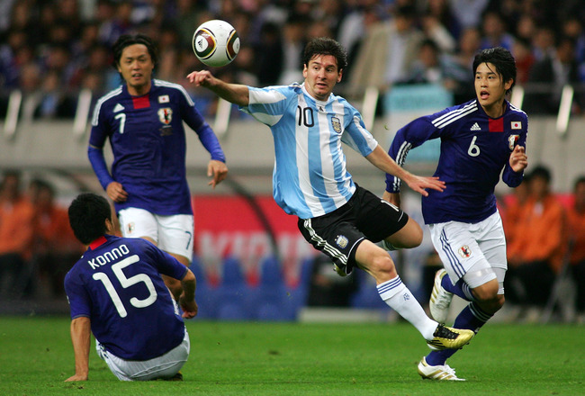 SAITAMA, JAPAN - OCTOBER 08: Lionel Messi  of Argentina  and Atsuto Uchida of Japan compete for the ball during  the International Friendly match between Japan and Argentina at Saitama Stadium on October 8, 2010 in Saitama, Japan. (Photo by Koji Watanabe/