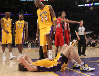 LOS ANGELES, CA - JANUARY 14: Kobe Bryant #24 of the Los Angeles Lakers checks on fallen teammate Pau Gasol #16 in the game against the New Jersey Nets at Staples Center on January 14, 2011 in Los Angeles, California. The Lakers won 100-88.  NOTE TO USER: