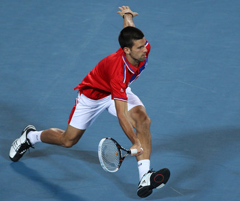 PERTH, AUSTRALIA - JANUARY 06:  Novak Djokovic of Serbia plays a return shot during his mixed doubles match against Justine Henin and Ruben Bemelmans of Belgium on day six of the Hopman Cup at The Burswood Dome on January 6, 2011 in Perth, Australia.  (Ph