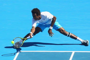 MELBOURNE, AUSTRALIA - JANUARY 15:  Gael Monfils of France stretches to play a forehand during his match against Lleyton Hewitt of Australia during day four of the AAMI Classic at Kooyong on January 15, 2011 in Melbourne, Australia.  (Photo by Quinn Roone