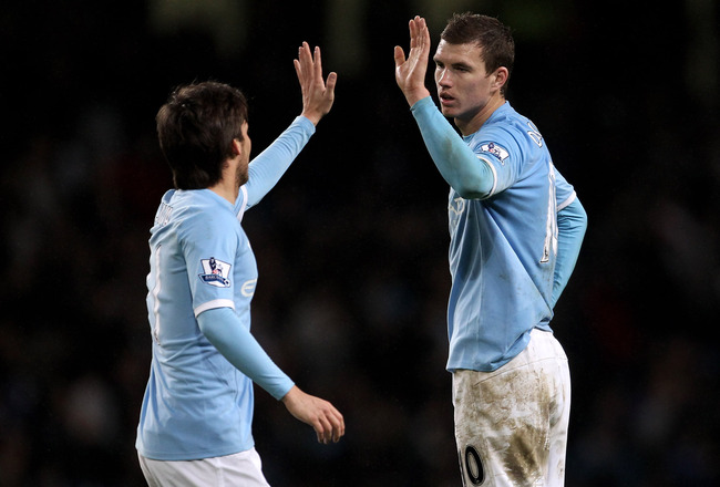 MANCHESTER, UNITED KINGDOM - JANUARY 15:   Edin Dzeko of Manchester City celebrates with team mate David Silva (L) at the end of the Barclays Premier League match between Manchester City and Wolverhampton Wanderers at the City of Manchester Stadium on Jan