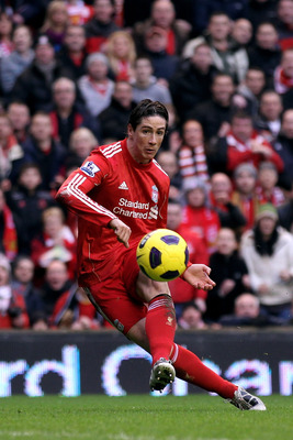 LIVERPOOL, ENGLAND - JANUARY 16:  Fernando Torres of Liverpool shoots past John Heitinga of Everton and subsequently hits the post during the Barclays Premier League match between Liverpool and Everton at Anfield on January 16, 2011 in Liverpool, England.