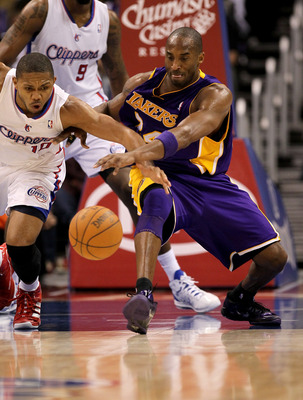 LOS ANGELES, CA - DECEMBER 08:  Kobe Bryant #24 of the Los Angeles Lakers battles to control a loose ball against Eric Gordon #10 of the Los Angeles Clippers at Staples Center on December 8, 2010 in Los Angeles, California.  The Lakers won 87-86.  NOTE TO