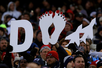 FOXBORO, MA - JANUARY 16:  New England Patriots fans hold up a signs prior to their 2011 AFC divisional playoff game against the New York Jets at Gillette Stadium on January 16, 2011 in Foxboro, Massachusetts.  (Photo by Elsa/Getty Images)