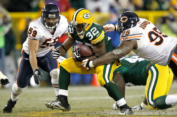 GREEN BAY, WI - JANUARY 02:  Kahlil Bell #32 of the Green Bay Packers carries the ball against Pisa Tinoisamoa #59 and Anthony Adams #95 of the Chicago Bears at Lambeau Field on January 2, 2011 in Green Bay, Wisconsin.  (Photo by Matthew Stockman/Getty Im
