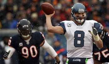 CHICAGO, IL - JANUARY 16:  Quarterback Matt Hasselbeck #8 of the Seattle Seahawks throws the ball as Julius Peppers #90 of the Chicago Bears attempts to run in for the sack in the first half in the 2011 NFC divisional playoff game at Soldier Field on Janu