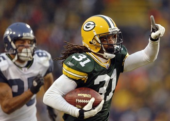 GREEN BAY, WI - JANUARY 4:  Al Harris#31 of the Green Bay Packers intercepts a pass and runs it in for the game-winning touchdown in overtime against the Seattle Seahawks on January 4, 2004 at Lambeau Field in Green Bay, Wisconsin. The Packers defeated th