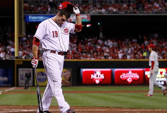 CINCINNATTI - OCTOBER 10: Joey Votto #19 of the Cincinnati Reds walks back to the dugout after striking out against Cole Hamels #35 of the Philadelpia Phillies, who also walks to the dugout, during game 3 of the NLDS at Great American Ball Park on October