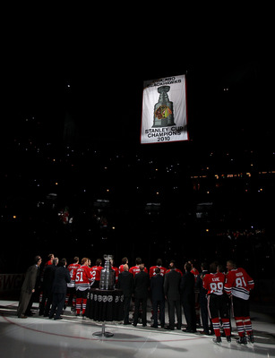 CHICAGO - OCTOBER 09: Members of the Chicago Blackhawks and their staff watch as the Stanley Cup Championship banner is raised during a ceremony before the Blackhawks season home opening game against the Detroit Red Wings at the United Center on October 9