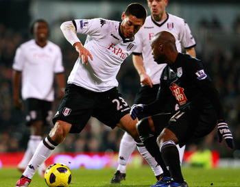 LONDON, ENGLAND - JANUARY 04:  Clint Dempsey (L) of Fulham battles for the ball with Youssouf Mulumbu of West Bromwich Albion during the Barclays Premier League match between Fulham and West Bromwich Albion at Craven Cottage on January 4, 2011 in London,