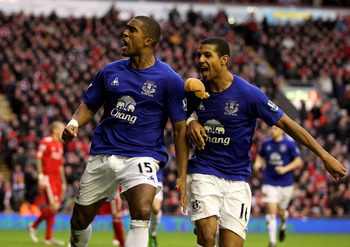 LIVERPOOL, ENGLAND - JANUARY 16:  Sylvain Distin of Everton celebrates scoring his team's first goal with team mate Jermaine Beckford (R) as a pie from the crowd flies towards them during the Barclays Premier League match between Liverpool and Everton at