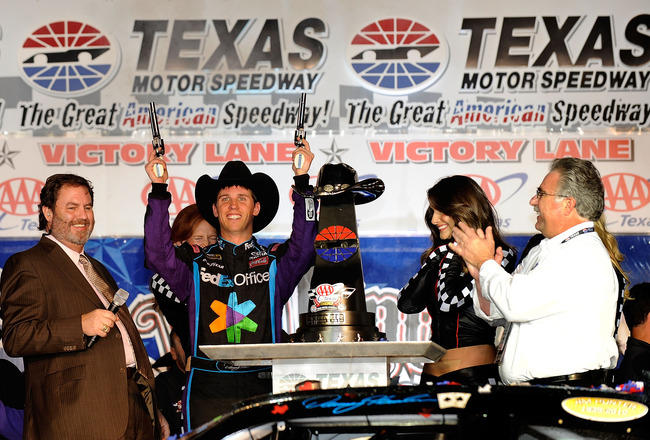 FORT WORTH, TX - NOVEMBER 07:  Texas Motor Speedway President Eddie Gossage (L) introduces Denny Hamlin (C), driver of the #11 FedEx Office Toyota, as he shoots a Turnbull Revolvers in Victory Lane after winning the NASCAR Sprint Cup Series AAA Texas 500