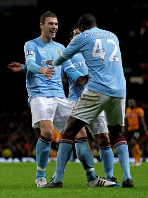 MANCHESTER, ENGLAND - JANUARY 15:  Yaya Toure of Manchester City celebrates scoring his team's third goal with team mates Edin Dzeko  (L) and Carlos Tevez during the Barclays Premier League match between Manchester City and Wolverhampton Wanderers at the