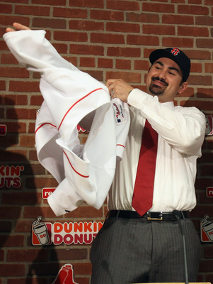 BOSTON, MA - DECEMBER 06:  Adrian Gonzalez puts on his jersey during a press conference after it was announced that he signed with the Boston Red Sox on December 6,  2010 at Fenway Park in Boston, Massachusetts.  (Photo by Elsa/Getty Images)