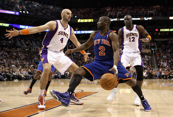 PHOENIX - JANUARY 07:  Raymond Felton #2 of the New York Knicks handles the ball under pressure from Marcin Gortat #4 and Mickael Pietrus #12 of the Phoenix Suns during the NBA game at US Airways Center on January 7, 2011 in Phoenix, Arizona. The Knicks d