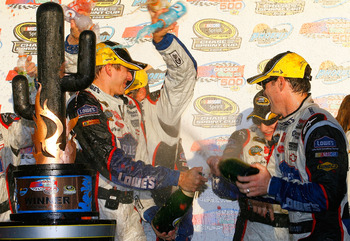 AVONDALE, AZ - NOVEMBER 15:  Jimmie Johnson (R), driver of the #48 Lowe's Chevrolet, and his crew celebrate in victory lane with champagne after winning the NASCAR Sprint Cup Series Checker O'Reilly Auto Parts 500 at Phoenix International Raceway on Novem