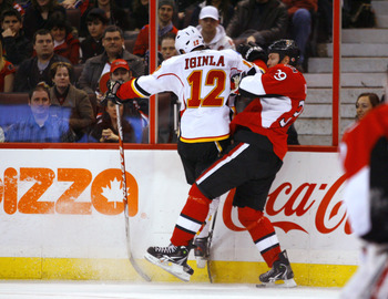 OTTAWA, ON - JANUARY 14:  Jarome Iginla #12 of the Calgary Flames throws a big hit on Matt Carkner #39 of the Ottawa Senators along the far boards in a game at Scotiabank Place on January 14, 2011 in Ottawa, Canada.  (Photo by Phillip MacCallum/Getty Imag