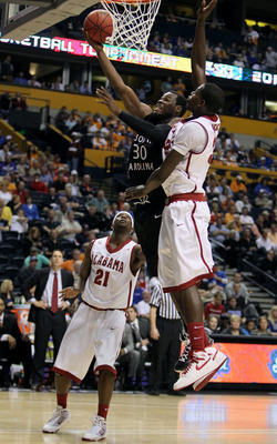 NASHVILLE, TN - MARCH 11:  Johndre Jefferson #30 of the South Carolina Gamecocks drives for a shot attempt against Jamychal Green #32 and Senario Hillman #21 of the Alabama Crimson Tide during the first round of the SEC Men's Basketball Tournament at the