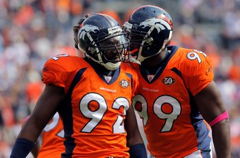DENVER - OCTOBER 04:  Elivs Dumervil #92 of the Denver Broncos celebrates with Vonnie Holliday #99 as they defend against the Dallas Cowboys during NFL action at Invesco Field at Mile High on October 4, 2009 in Denver, Colorado. The Broncos defeated the C