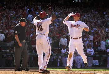 PHOENIX - APRIL 05:  Stephen Drew #6 of the Arizona Diamondbacks is congratulated by teammate Justin Upton #10 after hitting a 2 run inside the park home run against the San Diego Padres during the fourth inning of the Opening Day major league baseball ga