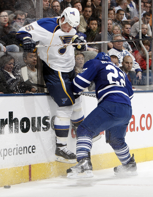 TORONTO, CANADA - JANUARY 6: Francois Beauchemin #22 of the Toronto Maple Leafs runs into Brad Winchester #15 of the St. Louis Blues during game action at the Air Canada Centre January 6, 2011 in Toronto, Ontario, Canada. (Photo by Abelimages/Getty Images