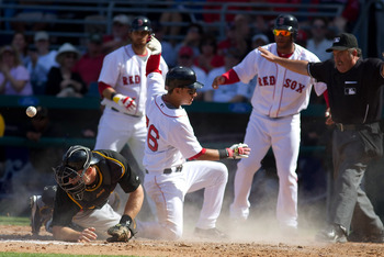 FORT MYERS, FL - MARCH 13:  Catcher Erik Kratz #67 of the Pittsburgh Pirates  cannot handle the throw as infielder Jose Iglesias #76 of the Boston Red Sox scores during a Grapefruit League Spring Training Game at City of Palms Park on March 13, 2010 in Fo