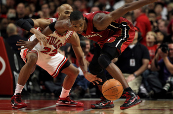 CHICAGO, IL - JANUARY 15:  Chris Bosh #1 of the Miami Heat battles for a loose ball with Taj Gibson #22 of the Chicago Bulls at the United Center on January 15, 2011 in Chicago, Illinois. The Bulls defeated the Heat 99-96. NOTE TO USER: User expressly ack