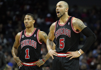 CHARLOTTE, NC - JANUARY 12:  Carlos Boozer #5 of the Chicago Bulls yells at a player as his teammate Derrick Rose #1 watches on against the Charlotte Bobcats during their game at Time Warner Cable Arena on January 12, 2011 in Charlotte, North Carolina. NO