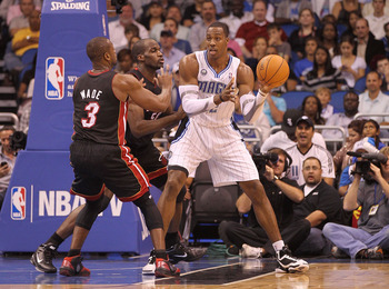 ORLANDO, FL - NOVEMBER 24:  Dwight Howard #12 of the Orlando Magic passes over Dwyane Wade #3 of the Miami Heat during a game at Amway Arena on November 24, 2010 in Orlando, Florida. NOTE TO USER: User expressly acknowledges and agrees that, by downloadin