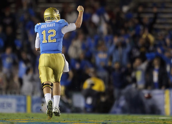 PASADENA, CA - DECEMBER 04:  Quarterback Richard Brehaut #12 of the UCLA Bruins celebrates Johnathan Franklin's (not pictured) touchdown in the first half against the USC Trojans at the Rose Bowl on December 4, 2010 in Pasadena, California.  (Photo by Jef