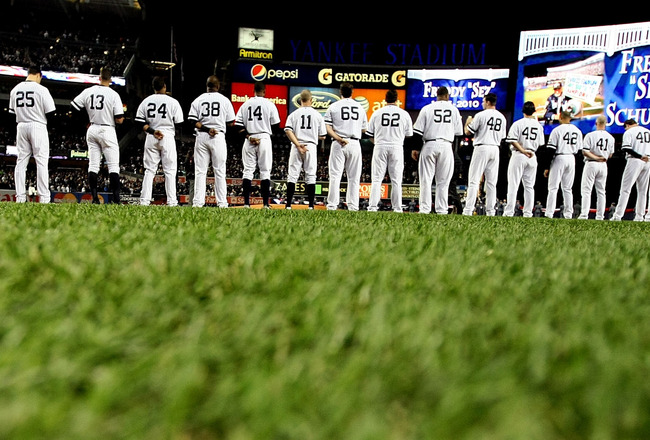 NEW YORK - OCTOBER 18:  Members of the New York Yankees stand in silence as they remember deceased Yankee fan Freddy 'Freddy Sez' Schuman before playing against the Texas Rangers in Game Three of the ALCS during the 2010 MLB Playoffs at Yankee Stadium on