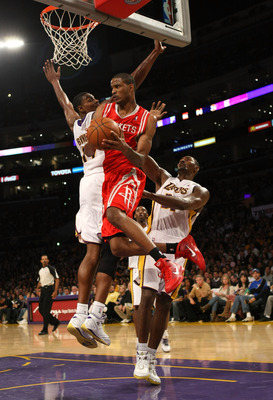 LOS ANGELES - NOVEMBER 15: Trevor Ariza #1 of  the Houston Rockets jumps through the lane between Ron Artest #37 and Andrew Bynum #17 of the Los Angeles Lakers on November 15, 2009 at Staples Center in Los Angeles, California.  The Rockets won 101-91.  NO
