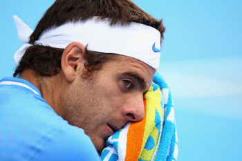MELBOURNE, AUSTRALIA - JANUARY 18:  Juan Martin Del Potro of Argentina towels down during his first round match against Dudi Sela of Israel during day two of the 2011 Australian Open at Melbourne Park on January 18, 2011 in Melbourne, Australia.  (Photo b