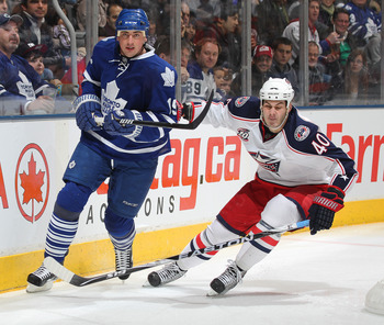 TORONTO,CAN - DECEMBER 30:  Jared Boll #40 of the Columbus Blue Jackets tries to get to Tomas Kaberle #15 of the Toronto Maple Leafs before he can clear the puck in a game on December 30, 2010 at the Air Canada Centre in Toronto, Canada. (Photo by Claus A