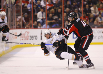 OTTAWA, ON - JANUARY 18:  Chris Phillips #4 of the Ottawa Senators throws a bodycheck on Corey Perry #10 of the Anaheim Ducks at centre ice in a game at Scotiabank Place on January 18, 2011 in Ottawa, Canada.  (Photo by Phillip MacCallum/Getty Images)