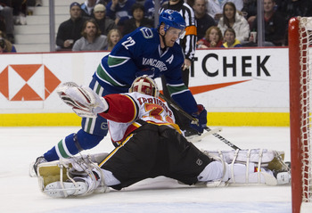 VANCOUVER, CANADA - JANUARY 5: Goalie Miikka Kiprusoff #34 of the Calgary Flames stretches out to stop Daniel Sedin #22 of the Vancouver Canucks during the second period in NHL action on January 05, 2011 at Rogers Arena in Vancouver, BC, Canada.  (Photo b