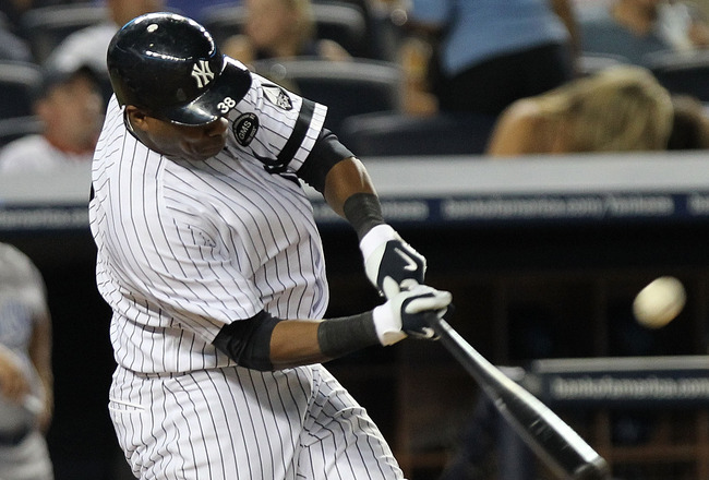 NEW YORK - JULY 22: Marcus Thames #38 of the New York Yankees hits a RBI sacrifice fly to score Jorge Posada #20 against the Kansas City Royals at Yankee Stadium on July 22, 2010 in the Bronx borough of New York City.  (Photo by Nick Laham/Getty Images)