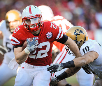 LINCOLN, NE - NOVEMBER 26: Rex Burkhead #22 of the Nebraska Cornhuskers runs past Michael Sipili #10 of the Colorado Buffaloes during the first half of their game at Memorial Stadium on November 26, 2010 in Lincoln, Nebraska.  (Photo by Eric Francis/Getty