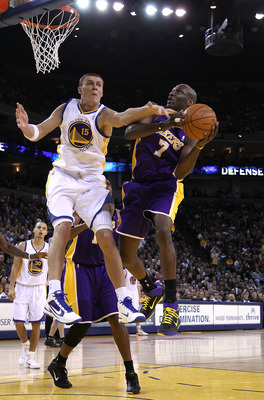OAKLAND, CA - JANUARY 12: Lamar Odom #7 of the Los Angeles Lakers is fouled by Andris Biedrins #15 of the Golden State Warriors at Oracle Arena on January 12, 2011 in Oakland, California. NOTE TO USER: User expressly acknowledges and agrees that, by downl
