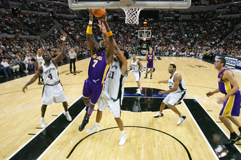 SAN ANTONIO - NOVEMBER 29:  Lamar Odom #7 of the Los Angeles Lakers takes the ball to the basket past Tim Duncan #21 of the San Antonio Spurs during a game at SBC Center on November 29, 2005 in San Antonio, Texas.  The Spurs defeated the Lakers 90-84.  NO