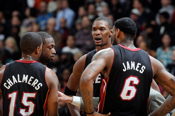 WASHINGTON, DC - DECEMBER 18:  Chris Bosh #1 of the Miami Heat talks with LeBron James #6, Dwyane Wade #3 and Mario Chalmers #15 during the game against the Washington Wizards at the Verizon Center on December 18, 2010 in Washington, DC. NOTE TO USER: Use