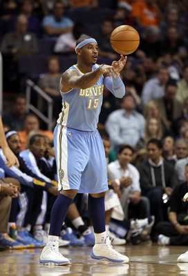 PHOENIX - NOVEMBER 15:  Carmelo Anthony #15 of the Denver Nuggets passes the ball during the NBA game against the Phoenix Suns at US Airways Center on November 15, 2010 in Phoenix, Arizona.  The Suns defeated the Nuggets 100-94.  NOTE TO USER: User expres
